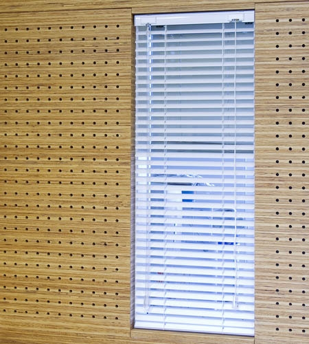 Plexwood® St. Olav's wall detail of cnc perforated acoustic veneer wood panels in pine with internal window