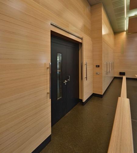 Plexwood® WBG Erfurt, detail van de geïntegreerde wand bekleding en verwerkte schuifdeuren van enkel-laags beuken fineer