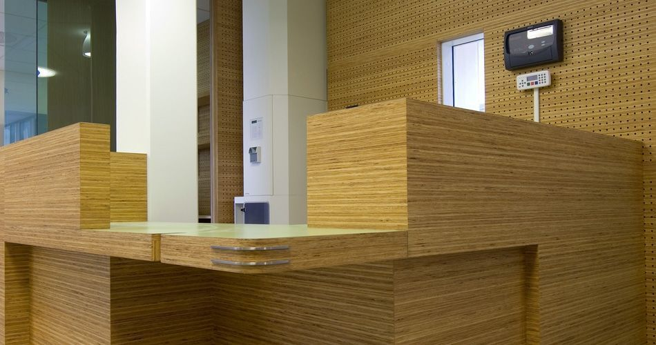 Plexwood® St. Olavs reception desk detail with cnc routed acoustic perforations back wall paneling in pine