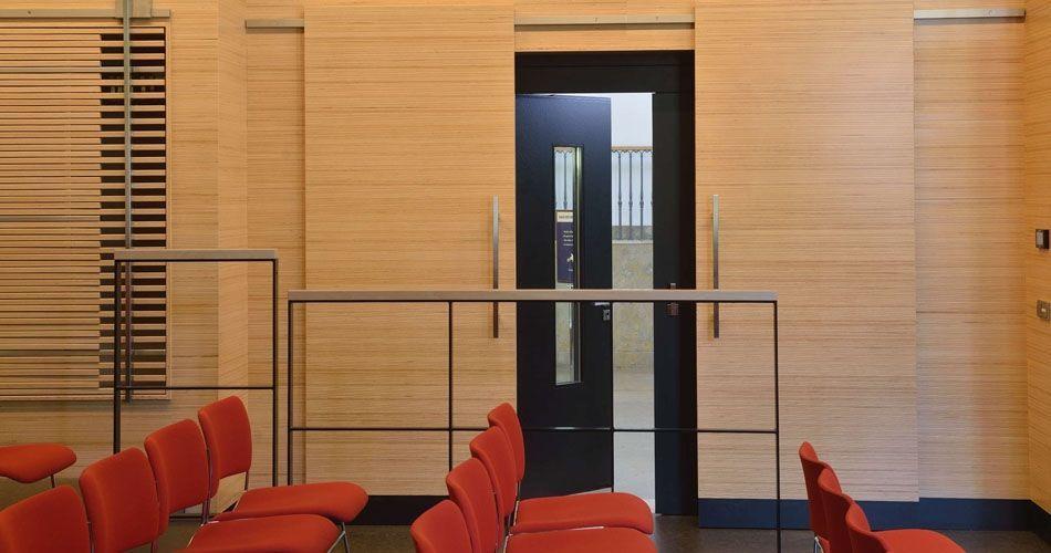 Plexwood® Salão para apresentações na WBG Erfurt com revestimento de paredes, portas de correr e portas semitransparentes características do guarda-roupa
